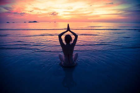Photo for Yoga silhouette, exercises on the beach. - Royalty Free Image