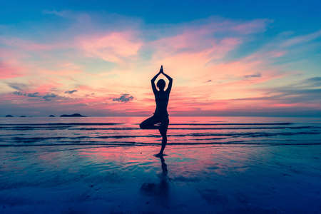 Foto de Silhouette of woman standing at yoga pose on the beach during an amazing sunset. - Imagen libre de derechos