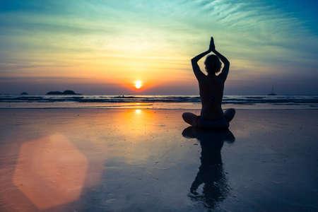Photo pour Female silhouette in Yoga meditation pose at amazing sunset. - image libre de droit