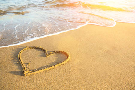 Foto de Heart drawn on the sand of a sea beach, soft wave and solar glare. - Imagen libre de derechos