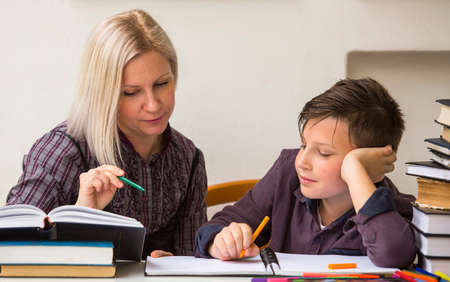 Photo for Schoolboy studying with the help of a tutor. - Royalty Free Image