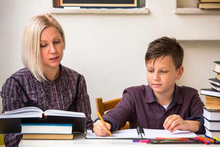 Foto de Young student learns at home with a his mom tutor. - Imagen libre de derechos