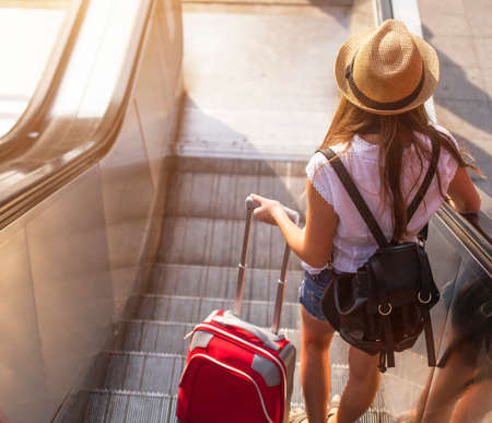 Photo pour Young girl with suitcase down the escalator. - image libre de droit