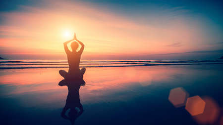 Foto de Silhouette meditation girl on the background of the sea and sunset. Yoga and healthy lifestyle. - Imagen libre de derechos