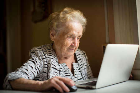 Foto per Old woman sitting with laptop at table in his house. - Immagine Royalty Free