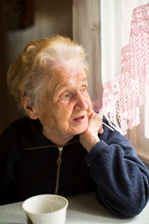 Foto de An elderly lady sitting near the window in the kitchen. - Imagen libre de derechos
