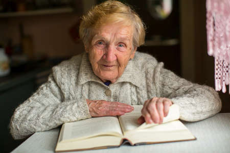 Foto für Old woman reading a book sitting at the table. - Lizenzfreies Bild