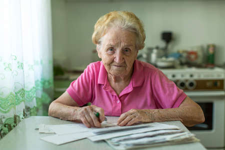 Photo pour An elderly woman fills the bill for utilities sitting at the table in the kitchen. - image libre de droit