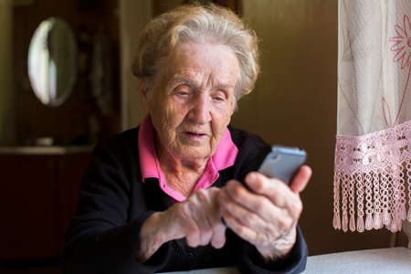 Foto de Elderly woman typing on the smartphone. - Imagen libre de derechos