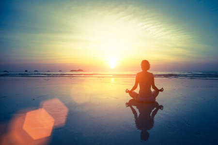 Photo pour Silhouette meditation yoga woman on the background of the sea and amazing sunset. Healthy lifestyle. - image libre de droit