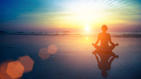 Photo pour Young woman silhouette practicing yoga on the beach at amazing sunset. - image libre de droit