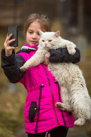 Little girl makes a selfie with the cat on the phone, outdoors.