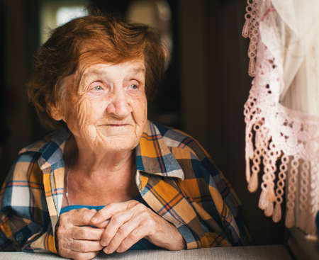 Photo for An elderly woman is looking out the window. - Royalty Free Image