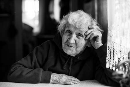 Foto de Elderly woman sitting at the table. Black and white portrait. - Imagen libre de derechos
