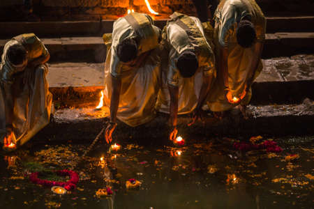 Foto de VARANASI, INDIA - MAR 17, 2018: Presenting flowers and candles to holy Ganges river. According to legends, the city was founded by God Shiva about 5000 years ago. - Imagen libre de derechos
