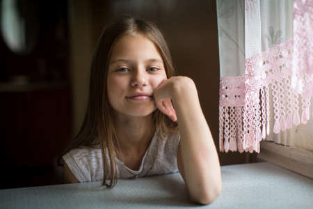 Photo for Portrait of cute ten-year-old girl sitting at the table. - Royalty Free Image