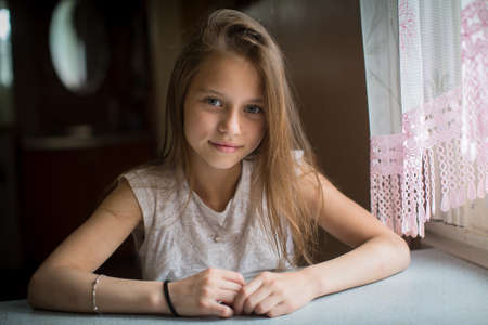Photo for Portrait of cute little girl sitting at the table. - Royalty Free Image