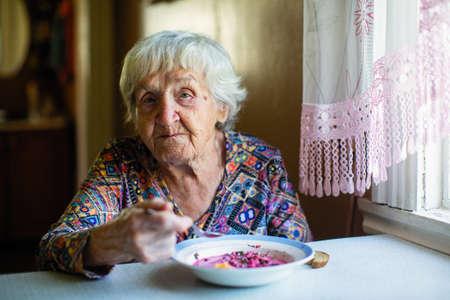 Photo pour An elderly woman eating soup sitting at a table in the house. - image libre de droit