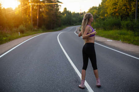 Photo pour Running woman warms up before jogging on the road. - image libre de droit