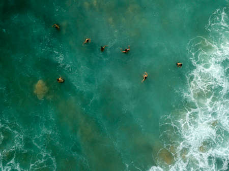 Photo pour People are swimming on waves in ocean, on Dreamland beach. Waves with white foam. Aerial photo. Bali, Indonesia. - image libre de droit