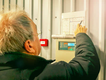 Foto de elderly Caucasian repairman engineer of fire alarm system.  Inspecting And Testing fire alarm panel. technician on the job checking projects - Imagen libre de derechos