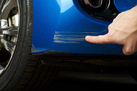 Photo for Car paint scratch close-up. Finger show scratch on blue car - Royalty Free Image