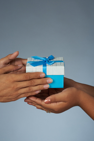Photo for Hands give and take gift blue box with ribbon close up view - Royalty Free Image