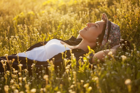 Foto de The girl in a hat dremet among wildflowers at sunset - Imagen libre de derechos