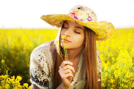 Foto de Happy girl in a hat enjoying the smell of the flower - Imagen libre de derechos