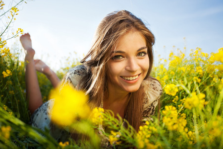 Cute happy girl lies among yellow wildflowers
