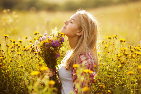 Beautiful blonde girl among the wildflowers in summer