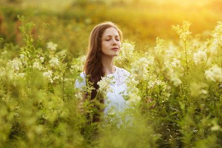 Photo for Happy beautiful girl stands among wildflowers and dreams - Royalty Free Image