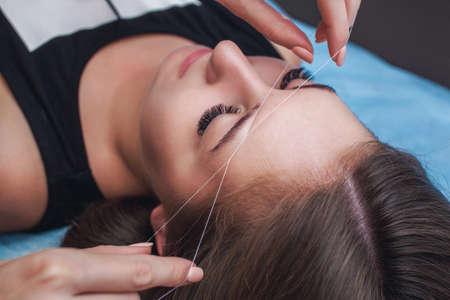 Foto de Master corrects makeup, gives shape and thread plucks eyebrows in a beauty salon. Professional care for face and eyebrows. - Imagen libre de derechos