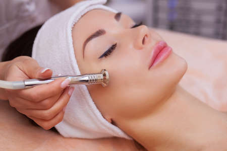 Photo pour The doctor-cosmetologist makes the procedure Microdermabrasion of the facial skin of a beautiful, young woman in a beauty salon.Cosmetology and professional skin care. - image libre de droit
