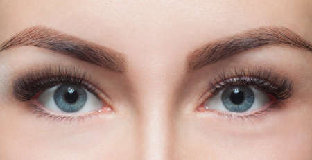 Photo for Eyelash removal procedure close up. Beautiful Woman with long lashes in a beauty salon. Look at the camera. - Royalty Free Image