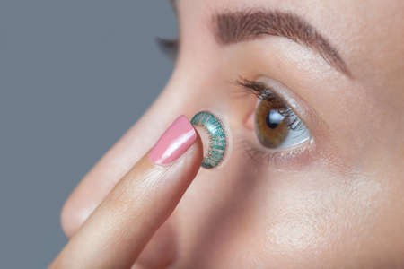 Foto de woman holds a blue contact lens on her finger. Eye care and the choice between the means to improve vision. - Imagen libre de derechos
