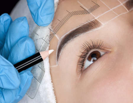 Foto de Permanent make-up for eyebrows of beautiful woman with thick brows in beauty salon. Closeup beautician doing  tattooing eyebrow. - Imagen libre de derechos