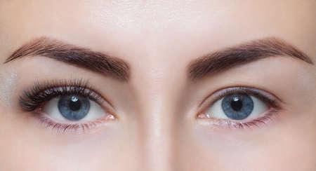 Foto de Eyelash extension procedure close up. Beautiful Woman with long lashes in a beauty salon. - Imagen libre de derechos