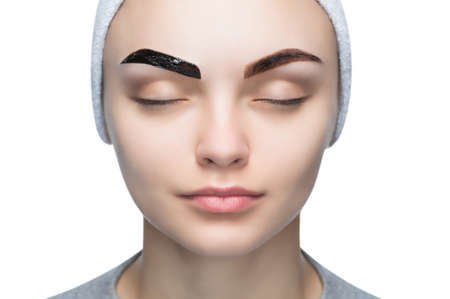 Foto de Portrait of a woman with beautiful, well-groomed eyebrows, makeup artist applies paint henna on eyebrows a beauty salon. Professional eyebrow care, dyeing and permanent make-up. - Imagen libre de derechos