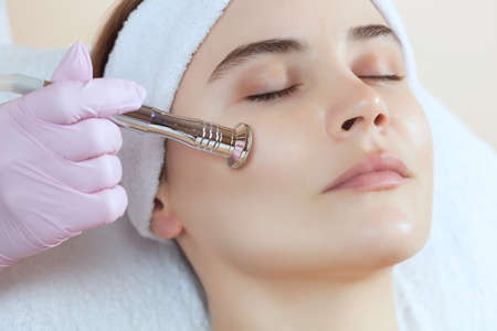 Photo pour The cosmetologist makes the procedure Microdermabrasion of the facial skin of a beautiful, young woman in a beauty salon.Cosmetology and professional skin care. - image libre de droit
