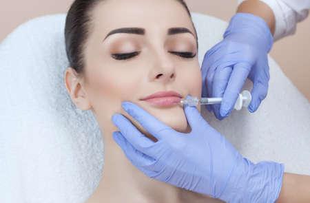 Foto de The doctor cosmetologist makes Lip augmentation procedure of a beautiful woman in a beauty salon.Cosmetology skin care. - Imagen libre de derechos
