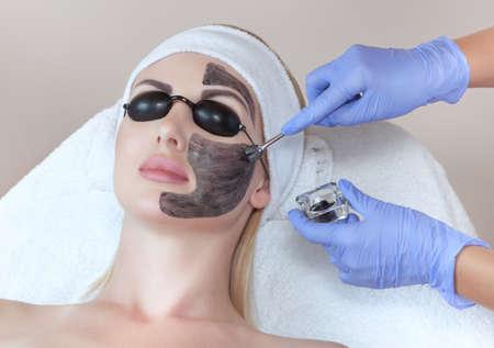 Photo pour Carbon face peeling procedure in a beauty salon. Hardware cosmetology treatment. - image libre de droit