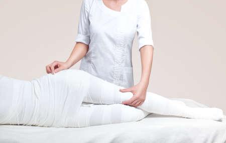 Photo pour The cosmetologist wraps the leg of the customer. Anti-cellulite procedure-STYX wrap. - image libre de droit