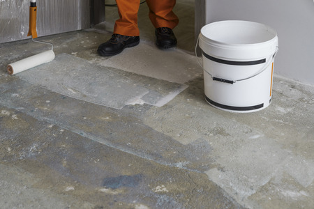 Photo for Man puts primer with roller on concrete floor. House under construction - Royalty Free Image