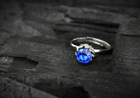 Photo pour jewellery ring witht blue sapphir on dark coal background, soft focus - image libre de droit