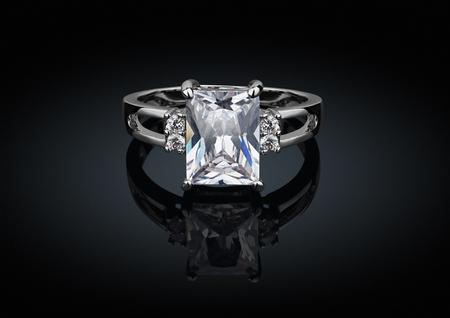 Foto de jewelry ring with big square diamond on black background with reflection - Imagen libre de derechos