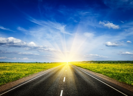 Photo pour Travel concept background - road in blooming spring meadow on sunset - image libre de droit