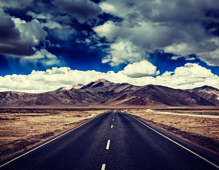 Vintage retro effect filtered hipster style travel image of Travel forward concept background - road on plains in Himalayas with mountains and dramatic clouds. Manali-Leh road, Ladakh, Jammu and Kashmir, India