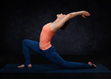 Foto de Beautiful sporty fit yogini woman practices yoga asana  Anjaneyasana - low crescent lunge pose in surya namaskar on dark background - Imagen libre de derechos