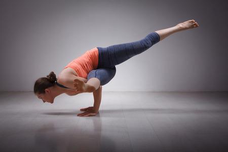 Foto de Beautiful sporty fit yogini woman practices yoga asana eka pada koundinyasana 1 - pose 1 dedicated to sage Koundinya pose in studio - Imagen libre de derechos